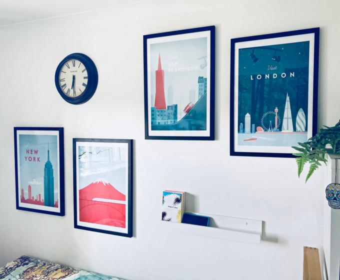 collection of travel posters by Henry Rivers on a white wall. New York, Japan, London, San Francisco with a wall clock