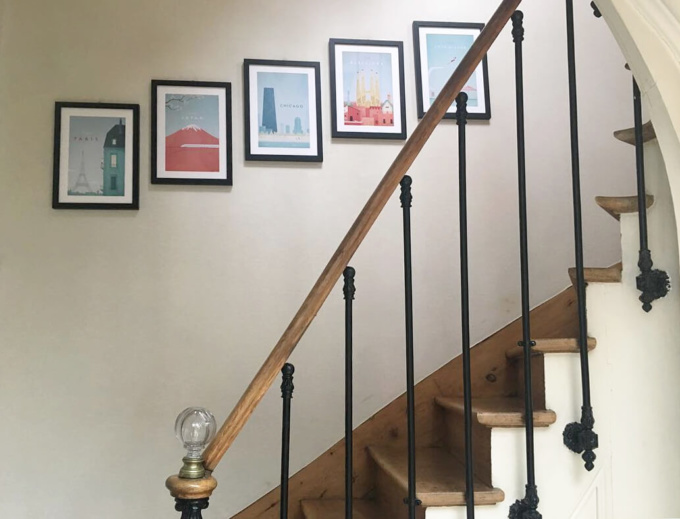Travel posters in a row. Artwork in black frames on stairs. Artworks by Henry Rivers.